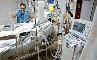 Vårdavdelning med säng, patient, dropp slangar, vårdare, mätinstrument